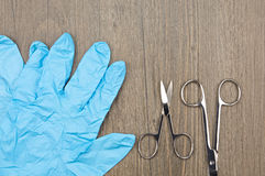 Close up silver surgical scissors and blue latex glove. Close up silver surgical scissors place beside blue latex glove on wood background Royalty Free Stock Images