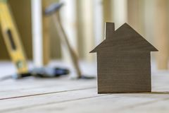 Close-up of simple small brown model house on blurred building t. Ools background. Construction, building and investments in real estate, property and ownership Royalty Free Stock Photography