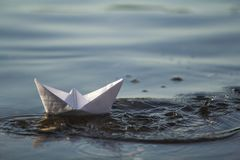 Close-up of simple small white origami paper boat floating in blue clear river or sea water under bright summer sky. Beauty of nat. Ure, freedom, dreams and Royalty Free Stock Photography
