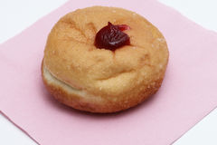 Close up single jam donut on pink napkin Royalty Free Stock Photo