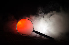 Close up Single Magnifying Glass with Black Handle, Leaning on the Wooden Table on orange red smoke dark background. Surreal backg Stock Photos