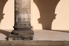 Close-up of single stone corinthian column and portico with blank wall. Plus sunlight with arch shadows - copy space Royalty Free Stock Photography