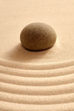 Close up of single stone in zen garden with sand Royalty Free Stock Photo