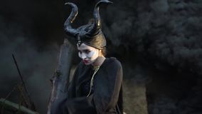 Close-up of sinister girl in the image Maleficent makes flapping cloak