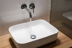Close up of sink and faucet on wooden shelf in white bathroom interior Stock Images