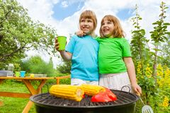 Close-up of sisters grilling corn with paprika Stock Images