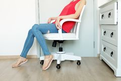 Close Up Sit on White Chair Studio. Beautiful Woman Wearing Red Shirt, Lack of Jeans and Shoes Sitting on a White Chair in the Roo Royalty Free Stock Images
