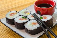 Close-up of six sushi rolls with soy sauce and chopsticks. A composition with six sushi rolls, a bowl of soy sauce and chopsticks Royalty Free Stock Images