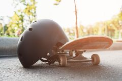 Close up skateboard and helmet, sport equipment. Summer extreme sport challenge and training background, protective sportswear in competition Royalty Free Stock Images