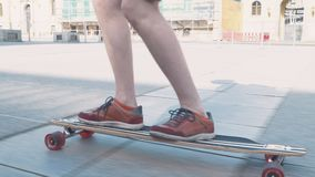 Close-up of a skateboard with men`s legs in sneakers extreme sports stock video footage