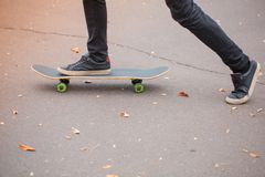 Close-up of a skateboarder`s foot in black sneakers. Stock Photo