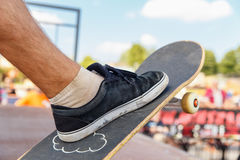Close-up of skater's leg on a skateboard Stock Images
