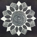 Gel pen hand drawn flower shape mandala. A close up of a sketch of a silver abstraction of a flower pattern on a dark grey background royalty free stock photos