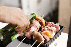 Oiling the Meat. Close up on skewed raw meat and vegetables, an adult's hand is pouring olive oil on it from a bottle, getting it ready for the grill Stock Images