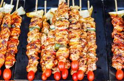 Close up skewers with pieces of grilled barbecue, green bell pepper, red tomato and meat for sell in street market,. Thailand royalty free stock photos
