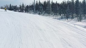 Close-up of ski slope and man in yellow jacket skiing on a track near coniferous forest in winter. Footage. Ski resort stock footage