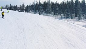 Close-up of ski slope and people skiing and snowboarding on a ski track near coniferous forest in winter. Footage. Ski stock video