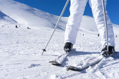 Close up of a skier's feet with ski poles. Royalty Free Stock Image