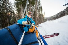 Close-up skier guy with ski sitting at ski-chair lift Stock Image
