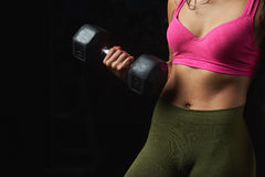 Close up of skinny young woman torso. Holding dumbbell isolated on black background Stock Photography