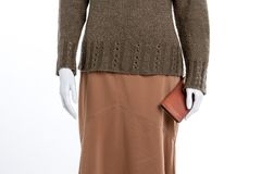 Close up skirt, sweater and wallet. Female mannequin with knitted pullover, brown skirt and purse close up. Female clothing and accessories Stock Photos
