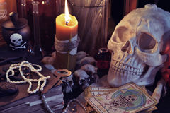 Close up of skull, candle and the tarot cards. Close up of scary skull, burning candle, old book, jewelry and tarot card The Death.  Halloween or esoteric Stock Image