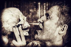 Close-up skull. Close-up portrait of an old medieval scientist holding a skull. Alchemist. Halloween Royalty Free Stock Photos