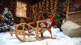 Close-up of the sled on the background of a wooden house with twinkling garlands. Closeup of a wooden sled in the snow near a Christmas tree on a background of a stock video footage