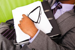 Close up of sleeping businessmans hand holding folder Royalty Free Stock Photography