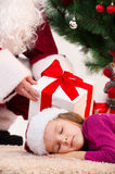 Close up of sleeping little girl under Christmas tree. Stock Photography