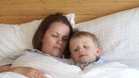 Close-up of sleepy mom and son lying on white pillows on the bed in the bedroom. Close-up of sleepy mom and son lying on white pillows on the bed in the bedroom stock footage