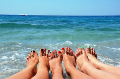 Close up of slender legs of three young girls. Blue sea in the background, the concept of a beach holiday.  Royalty Free Stock Images
