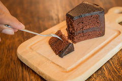 Close up Slice of chocolate cake with frok on wood table. Slice of chocolate cake with frok on wood table Royalty Free Stock Photography