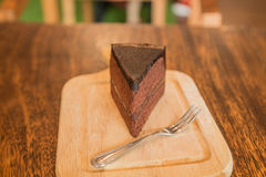 Close up Slice of chocolate cake with frok on wood table. Slice of chocolate cake with frok on wood table Stock Photos