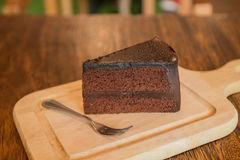 Close up Slice of chocolate cake with frok on wood table. Slice of chocolate cake with frok on wood table Royalty Free Stock Images