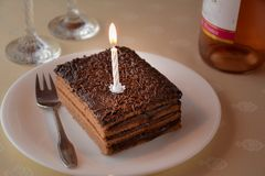 Slice of a layered chocolate cake with one candle and two glasse Royalty Free Stock Images