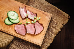 A close-up of sliced beef steak with a cucumber on a cutting board on a wooden background. Close-up of sliced beef steak with cucumber on a cutting board on a Royalty Free Stock Images