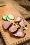 A close-up of sliced beef steak with a cucumber on a cutting board on a wooden background. Close-up of sliced beef steak with cucumber on a cutting board on a Stock Image