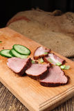 A close-up of sliced beef steak with a cucumber on a cutting board on a wooden background. Close-up of sliced beef steak with cucumber on a cutting board on a Stock Photo