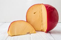 Close up. Sliced Head of Cheese Edam on white wooden background stock photo