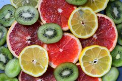 Close up sliced fruits on the wood background. Close up sliced lemon , kiwi and grape fruit on the wood background Royalty Free Stock Image