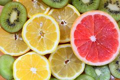 Close up sliced fruits on the wood background. Close up sliced lemon , kiwi and grape fruit on the wood background Royalty Free Stock Photo