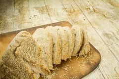 Close-up of a sliced  loaf of homemade bread with sesame seeds on wooden cutting board in selective focus on wooden table royalty free stock image