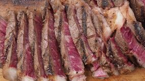 Close up sliced medium rare beef steak meat on wooden cutting board.