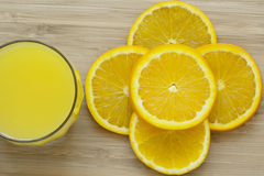 Close up of sliced orange and a full glass of orange juice on wooden surface Stock Photo