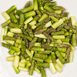 Close up on sliced pieces of green asparagus on a white plate Stock Image