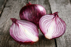Close up of sliced red onion and whole red onion on a wooden tab. Le Royalty Free Stock Photo