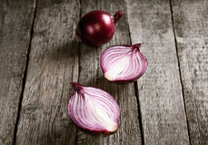 Close up of sliced red onion and whole red onion. On a wooden table Royalty Free Stock Image