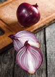 Close up of sliced red onion and whole red onion. On a wooden table stock photography