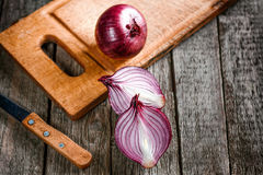 Close up of sliced red onion. And whole red onion on a wooden table stock image